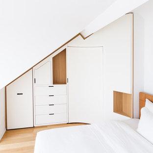 Diseño de armario unisex, contemporáneo, grande, con armarios con rebordes decorativos, puertas de armario blancas, suelo de madera clara y suelo beige