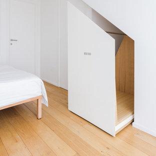 Immagine di un grande armadio o armadio a muro unisex design con ante a filo, ante bianche, parquet chiaro e pavimento beige