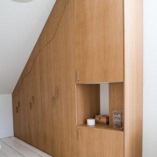 Immagine di un armadio o armadio a muro unisex nordico con ante in legno chiaro, pavimento in legno verniciato e pavimento bianco