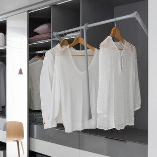 Réalisation d'un grand dressing room design neutre avec un placard sans porte et des portes de placard grises.