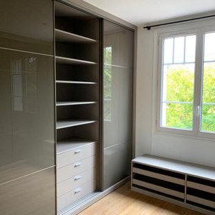 Foto di una cabina armadio unisex moderna di medie dimensioni con ante marroni, parquet chiaro e pavimento beige