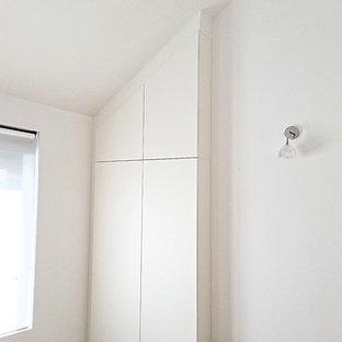 Diseño de armario unisex, actual, de tamaño medio, con armarios con rebordes decorativos, puertas de armario blancas y suelo de madera clara
