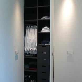 Réalisation d'un grand placard dressing design pour un homme avec un placard à porte plane, des portes de placard blanches et moquette.