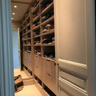 Ejemplo de vestidor unisex, clásico, pequeño, con armarios con rebordes decorativos, puertas de armario de madera en tonos medios y moqueta