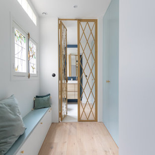 Modelo de armario vestidor unisex, actual, pequeño, con armarios con rebordes decorativos, puertas de armario azules, suelo de madera clara y suelo marrón
