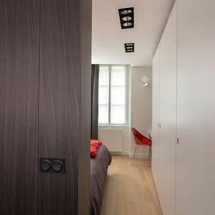 Esempio di un armadio incassato unisex minimal di medie dimensioni con ante a filo, ante grigie, parquet chiaro e pavimento beige