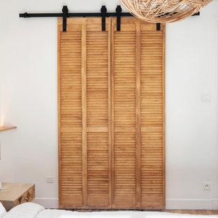 Foto di un piccolo spazio per vestirsi unisex industriale con ante a persiana, ante in legno chiaro, parquet chiaro e pavimento beige
