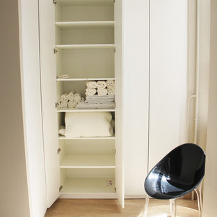 This is an example of a small midcentury gender-neutral built-in wardrobe in Lyon with beaded inset cabinets, white cabinets, light hardwood floors and beige floor.