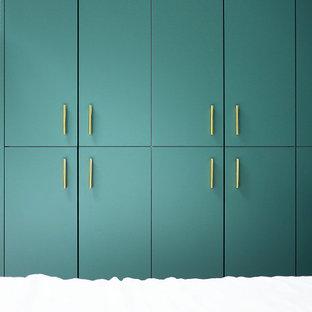 Diseño de armario vestidor unisex, moderno, de tamaño medio, con armarios con rebordes decorativos, puertas de armario azules, suelo de madera clara y suelo beige