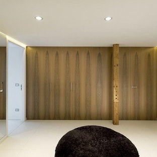 パリの広いモダンスタイルのおしゃれな収納・クローゼット (インセット扉のキャビネット、濃色木目調キャビネット、コンクリートの床、ベージュの床) の写真