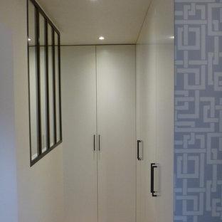 Idee per un armadio o armadio a muro unisex industriale di medie dimensioni con ante a filo, ante bianche, parquet chiaro e pavimento marrone