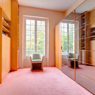 Immagine di uno spazio per vestirsi unisex minimal di medie dimensioni con ante di vetro, ante in legno chiaro, moquette e pavimento viola