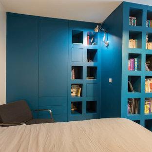 Foto de armario y vestidor de hombre, moderno, con puertas de armario azules y suelo de madera clara