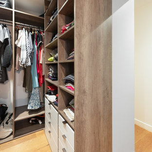 Photo of a medium sized contemporary gender neutral walk-in wardrobe in Lyon with open cabinets, medium wood cabinets, travertine flooring and beige floors.