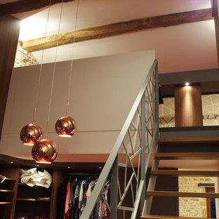 Idée de décoration pour un très grand dressing room design neutre avec des portes de placard en bois brun, moquette et un sol rouge.