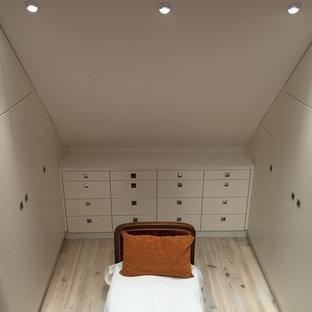 Foto de vestidor unisex, clásico renovado, de tamaño medio, con armarios con rebordes decorativos, puertas de armario blancas y suelo de madera clara