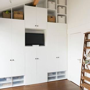 Cette photo montre un placard dressing tendance de taille moyenne et neutre avec un sol en bois brun et des portes de placard blanches.