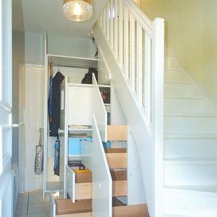 Foto di un armadio o armadio a muro unisex minimal con ante bianche, pavimento con piastrelle in ceramica e pavimento grigio