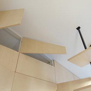 Foto di un piccolo armadio o armadio a muro unisex contemporaneo con ante a filo, ante in legno chiaro e parquet chiaro