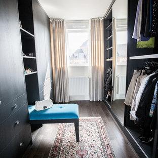 Cette photo montre un grand dressing room chic neutre avec des portes de placard en bois sombre et un sol en bois foncé.