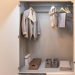 Cette image montre un placard dressing design de taille moyenne pour une femme avec un placard à porte plane et des portes de placard blanches.