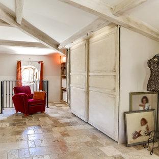 Modelo de armario y vestidor unisex, mediterráneo, grande, con armarios con rebordes decorativos, puertas de armario de madera clara y suelo beige