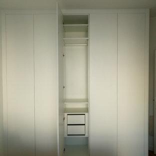 Imagen de armario unisex, moderno, de tamaño medio, con puertas de armario blancas, suelo de madera en tonos medios y suelo marrón