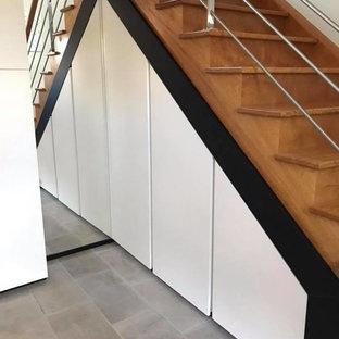 Imagen de armario unisex, minimalista, de tamaño medio, con armarios con rebordes decorativos, puertas de armario blancas, suelo de baldosas de cerámica y suelo gris