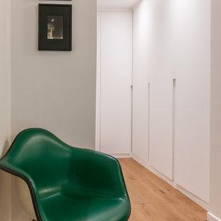 Cette image montre un dressing design neutre avec un placard à porte plane, des portes de placard blanches, un sol en bois brun et un sol marron.