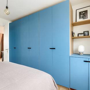 Ejemplo de vestidor unisex, actual, de tamaño medio, con puertas de armario azules y suelo de madera clara