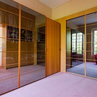 Inredning av ett modernt mellanstort klädskåp för könsneutrala, med luckor med glaspanel, skåp i ljust trä, heltäckningsmatta och lila golv