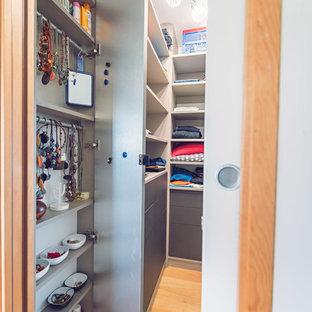 Imagen de armario vestidor unisex, contemporáneo, pequeño, con armarios abiertos, puertas de armario beige y suelo de madera clara