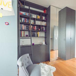 Foto de armario de mujer, urbano, de tamaño medio, con armarios con rebordes decorativos, puertas de armario grises y suelo de madera clara