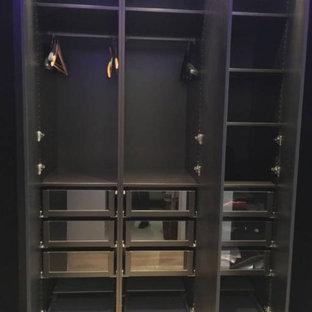 Ejemplo de vestidor unisex, minimalista, grande, con armarios con rebordes decorativos, puertas de armario de madera en tonos medios y suelo de madera en tonos medios