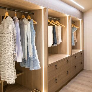 Exemple d'un armoire et dressing méditerranéen pour une femme avec un placard à porte plane, des portes de placard en bois brun, un sol en bois clair et un sol beige.