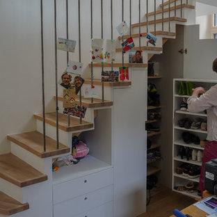 Foto di un piccolo armadio o armadio a muro unisex design con ante a filo, ante bianche, parquet chiaro e pavimento beige