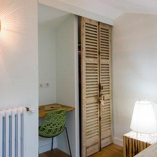 Ispirazione per un armadio o armadio a muro unisex chic con ante a persiana, ante in legno chiaro e parquet chiaro