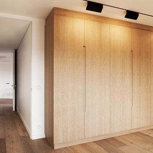 Modelo de armario unisex, actual, de tamaño medio, con suelo de madera clara y puertas de armario de madera clara