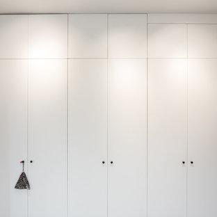 Diseño de armario unisex, minimalista, de tamaño medio, con armarios con rebordes decorativos y puertas de armario blancas