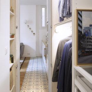 Cette photo montre un dressing et rangement tendance pour un homme avec un placard sans porte, des portes de placard en bois clair, un sol en carreau de terre cuite et un sol bleu.