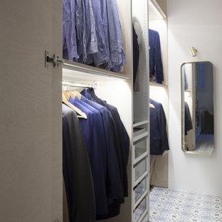 Esempio di una cabina armadio per uomo minimal di medie dimensioni con nessun'anta, ante in legno chiaro, pavimento in terracotta e pavimento blu