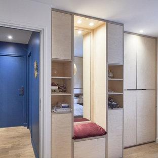 Ejemplo de armario unisex, pequeño, con armarios con rebordes decorativos, puertas de armario de madera clara y suelo de madera clara