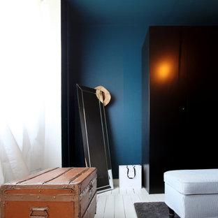Modelo de vestidor de hombre, contemporáneo, de tamaño medio, con armarios con rebordes decorativos, puertas de armario negras, suelo de madera pintada y suelo blanco