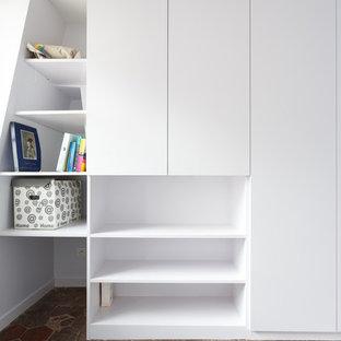 Imagen de armario unisex, de tamaño medio, con armarios con rebordes decorativos, puertas de armario blancas, suelo de baldosas de terracota y suelo rojo