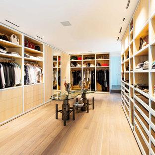 Idées déco pour un grand dressing contemporain neutre avec un sol en bois clair et un sol marron.