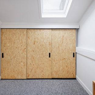 Immagine di un armadio o armadio a muro unisex industriale di medie dimensioni con ante a filo, ante in legno chiaro, moquette e pavimento grigio