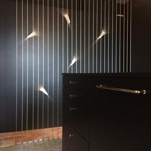 Diseño de vestidor de hombre, actual, pequeño, con armarios con rebordes decorativos, puertas de armario negras, suelo de baldosas de terracota y suelo gris