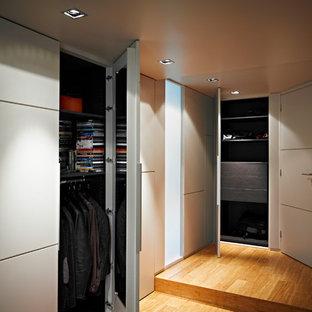 Modelo de vestidor unisex, actual, de tamaño medio, con armarios con rebordes decorativos, puertas de armario beige y suelo de bambú