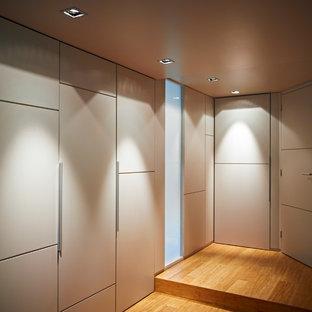 Ejemplo de vestidor unisex, contemporáneo, de tamaño medio, con puertas de armario beige, suelo de bambú y armarios con paneles lisos