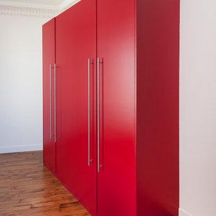 Modern inredning av ett stort klädskåp för könsneutrala, med röda skåp, mellanmörkt trägolv och beiget golv